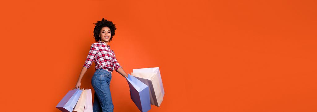 A educação financeira perpassa a revisão de gastos, mudanças de hábitos e limite com compras. Na foto, uma mulher sorridente segura sacolas