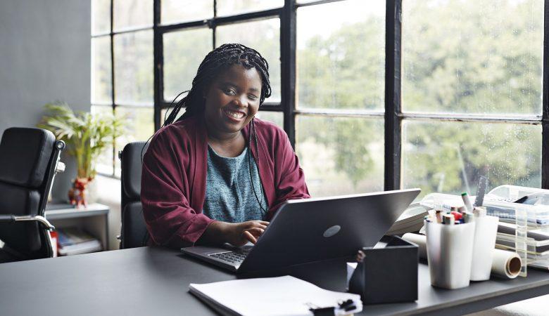 Mulher preta sorrindo, com um notebook na frente, em cima de uma mesa. Mostrando acessibilidade do ambiente de trabalho.